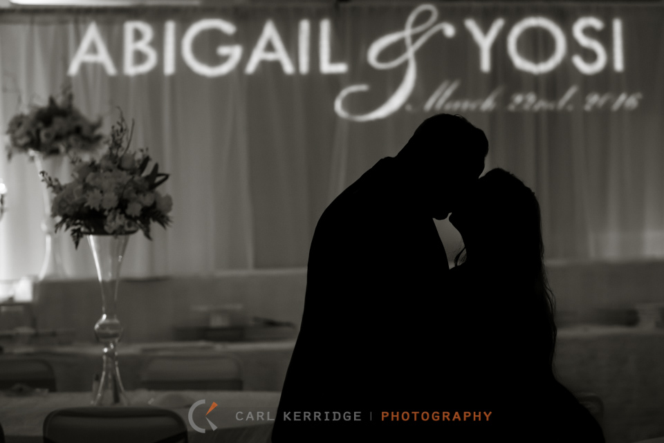 Myrtle Beach wedding, Fine art photography, wedding reception portrait at Hilton Myrtle Beach, silhouette of bride and groom kissing with their names in the background, name in lights on curtain in background