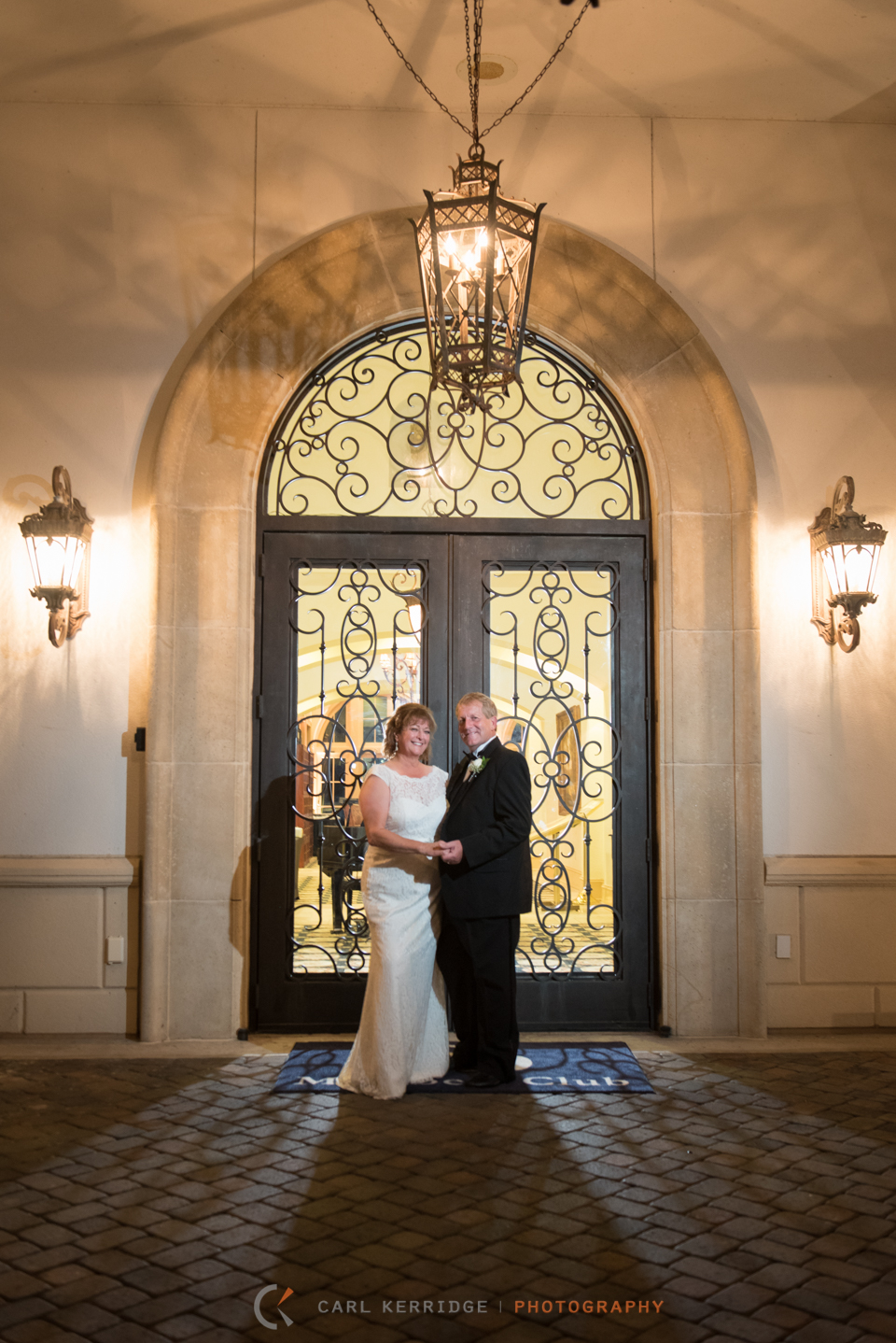 With an atmosphere of love and fun, the couple pose for a portrait in front of the big glass doors at the members club at grande dunes.