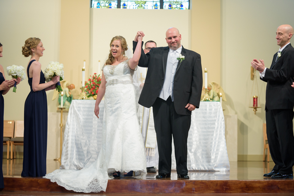 bride and groom put their hands in the air to celebrate being man and wife