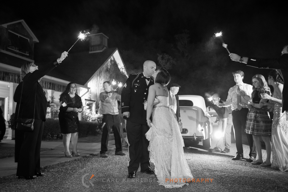 bride and groom walk out of the wedding reception and kiss after a sparkler exit