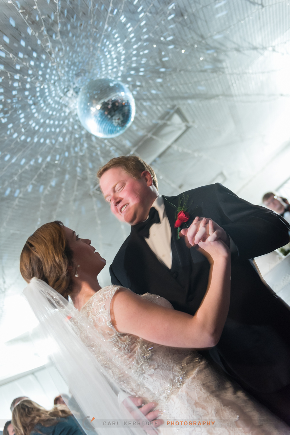 southern bride and her groom dance under a disco light at the wedding reception
